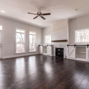На фото: открытая гостиная комната в стиле современная классика с белыми стенами, темным паркетным полом, стандартным камином, фасадом камина из вагонки, коричневым полом и стенами из вагонки с