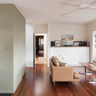 Diseño de salón abierto, actual, de tamaño medio, con paredes blancas, suelo de madera en tonos medios y televisor retractable