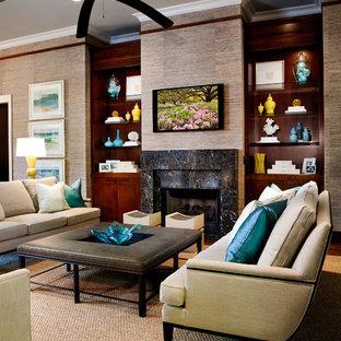 Foto de salón para visitas abierto, tropical, con chimenea tradicional, televisor colgado en la pared, suelo de madera oscura, marco de chimenea de piedra y paredes marrones
