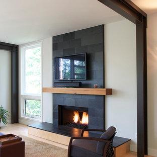 Immagine di un grande soggiorno minimal aperto con sala formale, pareti beige, parquet chiaro, camino classico, cornice del camino piastrellata e TV a parete