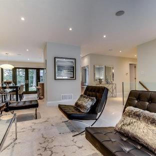 Foto di un grande soggiorno minimalista aperto con pareti grigie, pavimento in pietra calcarea, camino sospeso, cornice del camino in intonaco e TV a parete