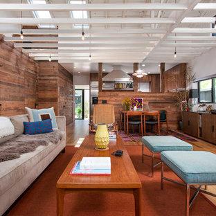 Modelo de salón abierto, actual, de tamaño medio, sin chimenea y televisor, con paredes marrones, suelo de madera clara y suelo amarillo