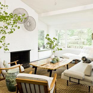 Immagine di un soggiorno etnico con pareti bianche, parquet scuro, camino classico e nessuna TV