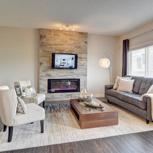 エドモントンの中くらいのトランジショナルスタイルのおしゃれなLDK (フォーマル、グレーの壁、クッションフロア、吊り下げ式暖炉、タイルの暖炉まわり、壁掛け型テレビ、黒い床) の写真