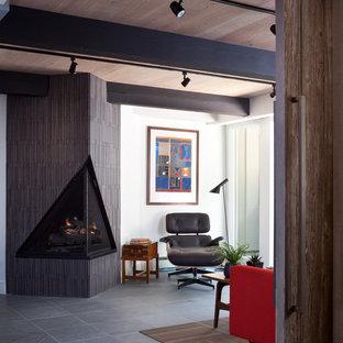 Foto de salón cerrado, retro, de tamaño medio, con paredes blancas, suelo de pizarra, marco de chimenea de baldosas y/o azulejos y chimenea de esquina