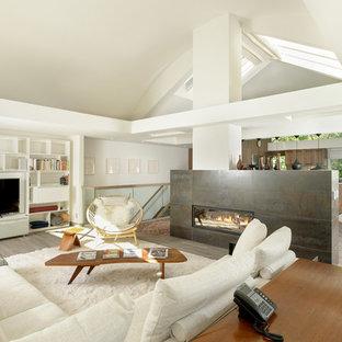Ispirazione per un soggiorno minimal di medie dimensioni e aperto con pareti bianche, pavimento in legno massello medio, camino bifacciale, cornice del camino piastrellata e parete attrezzata