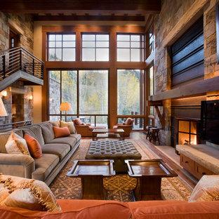 Modelo de salón abierto, actual, grande, con paredes beige, suelo de madera oscura, chimenea tradicional, marco de chimenea de metal, televisor colgado en la pared y suelo marrón