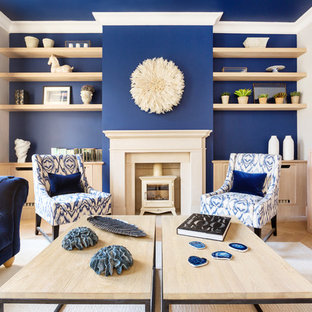 This is an example of a modern living room in London with blue walls, light hardwood flooring, a wood burning stove and beige floors.