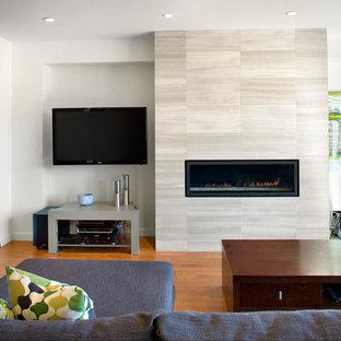 Imagen de salón abierto, moderno, con chimenea lineal, televisor colgado en la pared, paredes blancas, suelo de madera en tonos medios y marco de chimenea de piedra