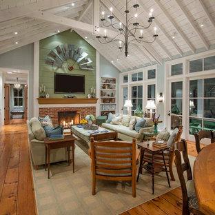 Diseño de salón abierto, campestre, con paredes grises, suelo de madera en tonos medios, chimenea tradicional, marco de chimenea de ladrillo y televisor colgado en la pared