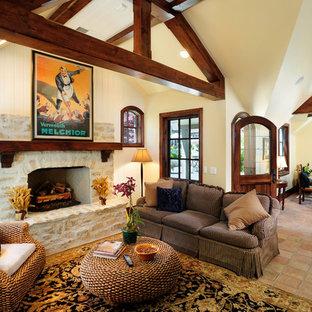 Foto di un ampio soggiorno classico aperto con cornice del camino in pietra, pareti gialle, pavimento in terracotta e camino classico