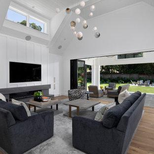 Réalisation d'un salon tradition ouvert avec un mur blanc, un sol en bois brun, une cheminée ribbon, un téléviseur fixé au mur, un sol marron, un plafond voûté, un plafond en lambris de bois et du lambris.