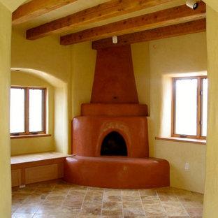Foto de salón cerrado, de tamaño medio, con paredes amarillas, suelo de travertino, estufa de leña y marco de chimenea de hormigón