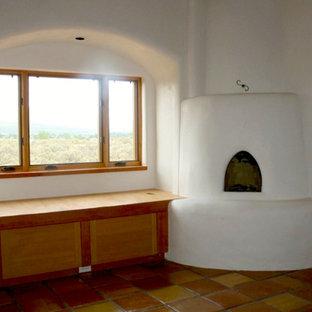 Diseño de salón cerrado, de tamaño medio, con paredes blancas, suelo de baldosas de terracota, estufa de leña y marco de chimenea de hormigón