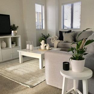 Modelo de salón abierto, moderno, pequeño, sin chimenea, con paredes blancas, moqueta, televisor independiente y suelo gris