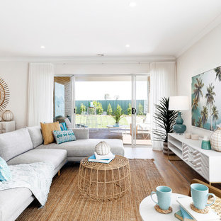 Beach style living room in Melbourne with white walls, medium hardwood floors and brown floor.