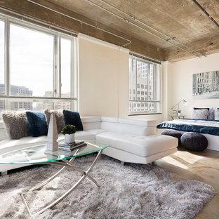 Exempel på ett litet industriellt allrum med öppen planlösning, med betonggolv, en väggmonterad TV och beige väggar