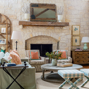 Mid-sized farmhouse formal and enclosed medium tone wood floor and brown floor living room photo in Austin with beige walls, a standard fireplace, a stone fireplace and no tv