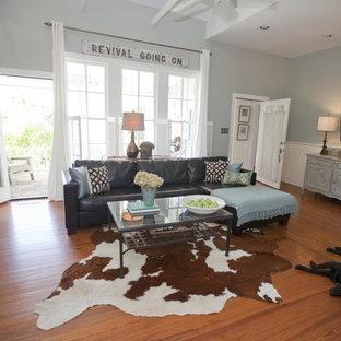 Landhaus Wohnzimmer mit blauer Wandfarbe und Wand-TV in Austin