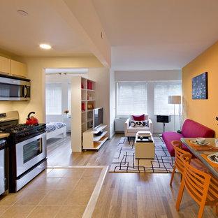 Imagen de salón para visitas abierto, actual, pequeño, con parades naranjas, suelo de madera clara y televisor independiente