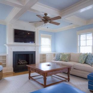 Idee per un soggiorno stile marinaro con pareti blu, parquet chiaro, camino classico e parete attrezzata
