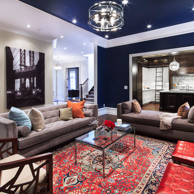 Large trendy open concept medium tone wood floor and brown floor living room photo in Toronto with blue walls, a standard fireplace and a wall-mounted tv