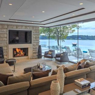 Idées déco pour un salon contemporain avec une cheminée standard, un manteau de cheminée en pierre, un téléviseur fixé au mur et un mur en pierre.