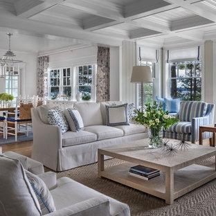 Imagen de salón cerrado, costero, con paredes blancas, suelo de madera oscura y suelo marrón
