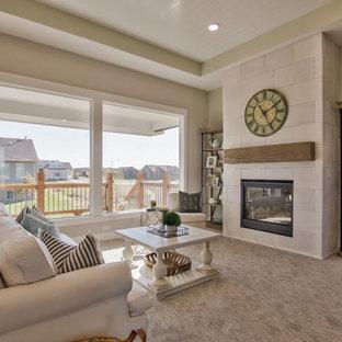 ウィチタの中くらいのカントリー風おしゃれなLDK (緑の壁、カーペット敷き、標準型暖炉、コンクリートの暖炉まわり、壁掛け型テレビ、グレーの床) の写真
