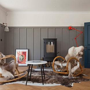 ロンドンの北欧スタイルのおしゃれなリビング (ベージュの壁、無垢フローリング、薪ストーブ、テレビなし) の写真