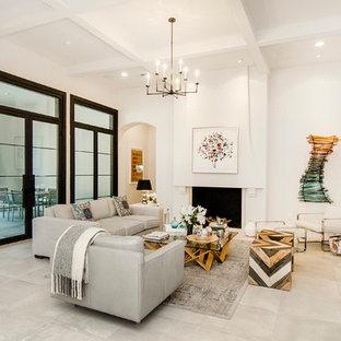Foto di un soggiorno mediterraneo con sala formale, pareti beige, pavimento in travertino, camino classico, cornice del camino in intonaco e TV a parete