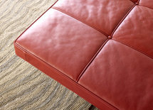 Who manufactures the gorgeous red leather bench/ottoman?