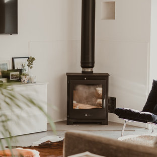 This is an example of a medium sized scandi open plan living room in Other with grey walls, concrete flooring, a wood burning stove, a wall mounted tv and grey floors.