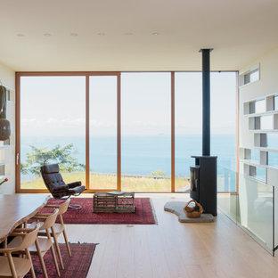 Diseño de salón abierto, vintage, de tamaño medio, con paredes blancas, suelo de madera clara, estufa de leña, marco de chimenea de metal y suelo beige