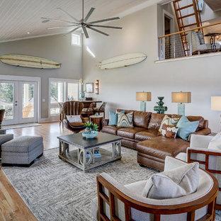 Modelo de salón abierto, costero, grande, con paredes grises y suelo de madera clara