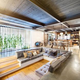 Modelo de salón para visitas abierto, urbano, grande, sin chimenea, con paredes multicolor, suelo de madera en tonos medios y televisor colgado en la pared
