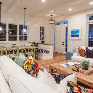 オレンジカウンティの大きいビーチスタイルのおしゃれなLDK (白い壁、無垢フローリング、標準型暖炉、コンクリートの暖炉まわり、テレビなし) の写真