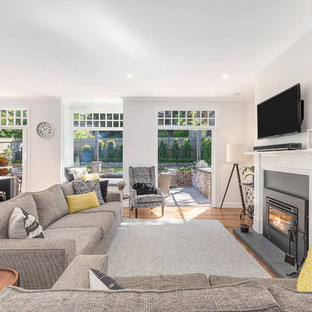 Mid-sized transitional formal open concept living room in Sydney with white walls, medium hardwood floors, a standard fireplace, a metal fireplace surround, a wall-mounted tv and brown floor.