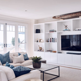 Photo of a beach style living room in Sydney with beige walls, light hardwood floors, a wall-mounted tv and brown floor.