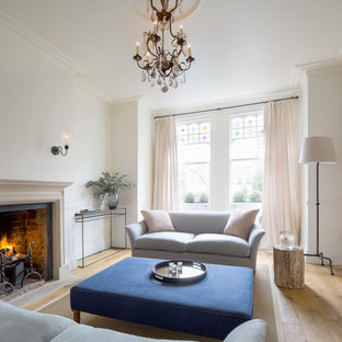 Medium sized classic formal living room in London with a standard fireplace, white walls, light hardwood flooring, no tv and beige floors.