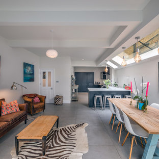 This is an example of a scandi open plan living room in London with white walls, concrete flooring and grey floors.