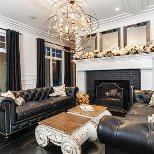 Klassisk inredning av ett vardagsrum, med vita väggar, mörkt trägolv, en standard öppen spis och en spiselkrans i tegelsten