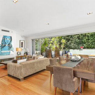 This is an example of a contemporary open concept living room in Sydney with white walls, medium hardwood floors, a ribbon fireplace and brown floor.