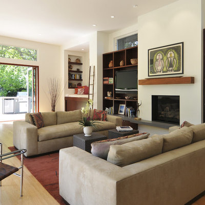 Inspiration for a contemporary open concept medium tone wood floor living room library remodel in San Francisco with a standard fireplace, white walls, a plaster fireplace and a media wall