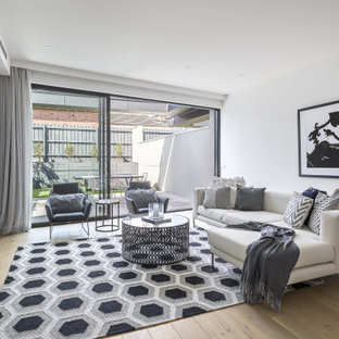 Design ideas for a contemporary open concept living room in Melbourne with white walls, light hardwood floors, a freestanding tv and beige floor.