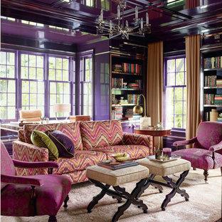 Modern inredning av ett separat vardagsrum, med ett bibliotek, lila väggar och mörkt trägolv