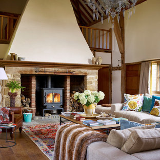 Design ideas for a country formal living room in London with white walls, medium hardwood flooring, a wood burning stove, no tv and brown floors.
