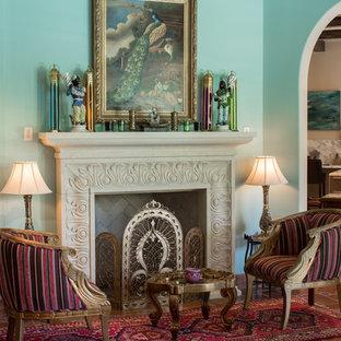 ヒューストンの地中海スタイルのおしゃれなリビング (フォーマル、青い壁、標準型暖炉、テレビなし、テラコッタタイルの床) の写真