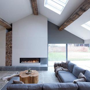 Idee per un grande soggiorno design con pareti bianche, pavimento in pietra calcarea, camino lineare Ribbon, cornice del camino in intonaco e sala formale
