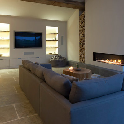 Example of a large trendy open concept limestone floor living room design in Cheshire with white walls, a corner fireplace and a plaster fireplace